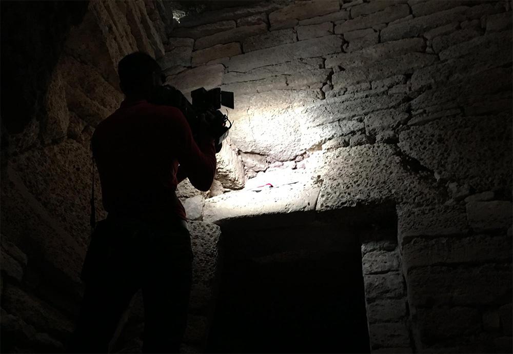 Dennis Keen's cameraman shoots a scene the dark depths of a holy site in Mangystau Region, Kazakhstan