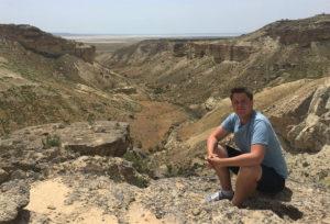 Dennis Keen sitting next to a canyon in Mangystau Region, Kazakhstan