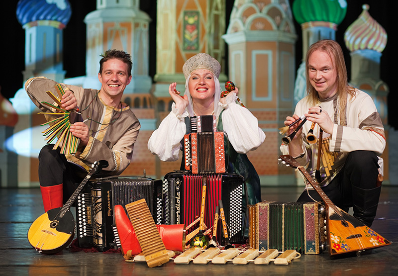 Russian folk ensemble Zolotoj Plyos kneels on stage behind a number of strange instruments