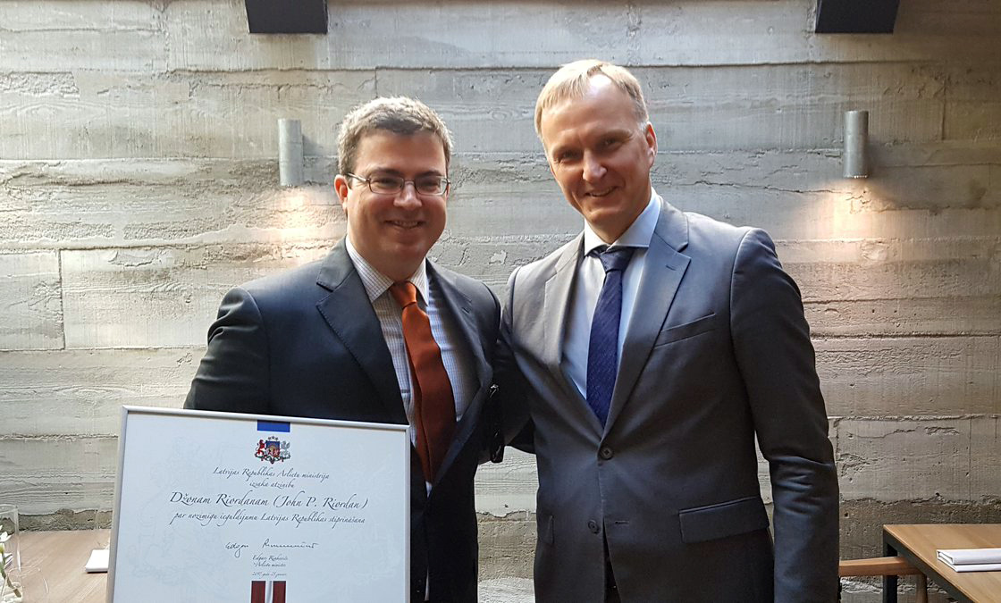 John Riordan presented with certificate from Latvian diplomat.